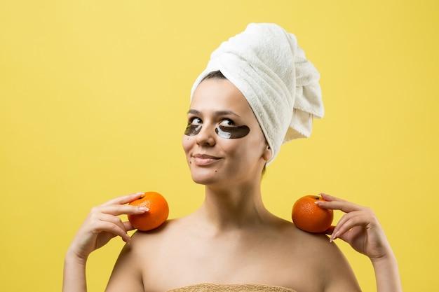 Młoda piękna dziewczyna w białym ręczniku na głowie nosi pod oczami plastry z żelu kolagenowego