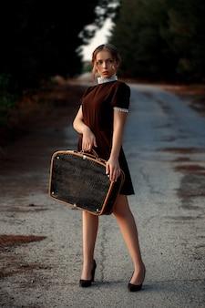 Młoda piękna dziewczyna w brązowej sukience w stylu retro stoi z czarną walizką w rękach na opuszczonej drodze.