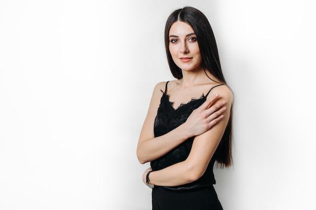 Młoda piękna dziewczyna w czarnych ubraniach na białej ścianie. miejsce na tekst