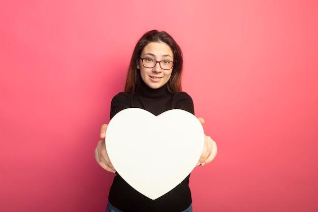 Młoda piękna dziewczyna w czarnym golfie i okularach pokazano pudełko w kształcie serca z uśmiechem na twarzy