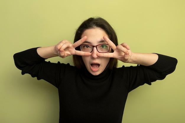 Młoda piękna dziewczyna w czarnym golfie i okularach robi znak v obiema rękami patrząc przez palce