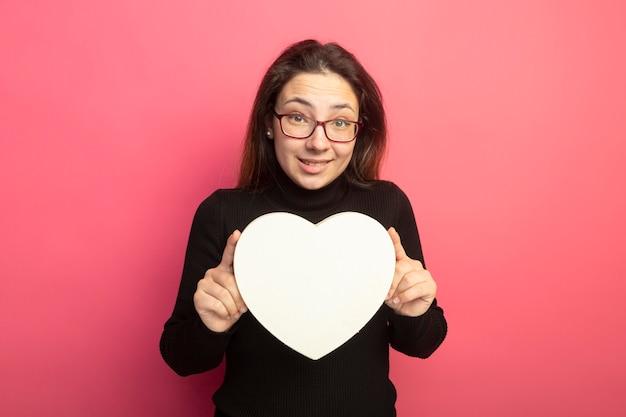 Młoda piękna dziewczyna w czarnym golfie i okularach, trzymając uśmiechnięte pudełko w kształcie serca