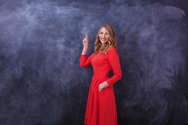 Młoda piękna dziewczyna w czerwonej sukience pokazuje gest rękami różne ludzkie emocje