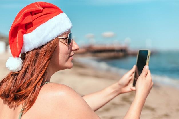 Młoda piękna dziewczyna w czerwonym kapeluszu świętego mikołaja i stroju kąpielowym sprawia, że selfie nad brzegiem morza