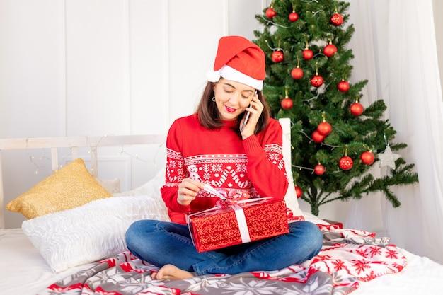Młoda piękna dziewczyna w czerwonym swetrze i kapeluszu prowadzi rozmowę wideo z prezentem