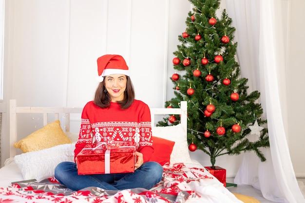 Młoda piękna dziewczyna w czerwonym swetrze i kapeluszu siedzi w domu na łóżku obok choinki z wielkim czerwonym prezentem