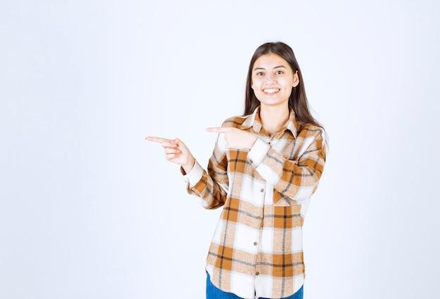 Młoda piękna dziewczyna w dorywczo strój stojący i pozowanie na białej ścianie.