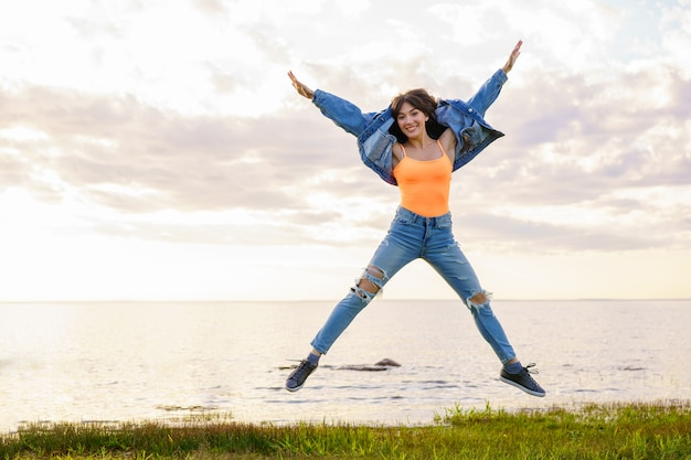 Młoda piękna dziewczyna w dżinsowej kurtce, dżinsach i żółtej koszulce skacze na tle morza w letni dzień, pozując o zachodzie słońca