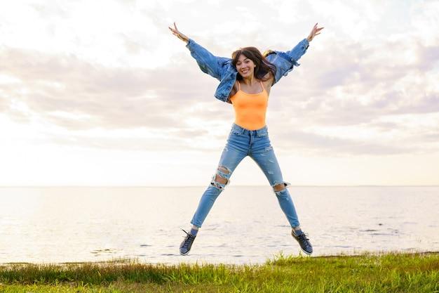 Młoda piękna dziewczyna w dżinsowej kurtce, dżinsach i żółtej koszulce skacze nad morzem w letni dzień, pozując o zachodzie słońca