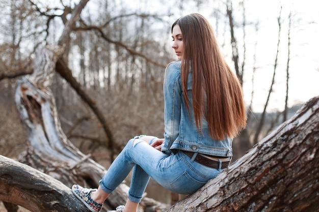 Młoda piękna dziewczyna w dżinsowej kurtce i dżinsach siedzi na drzewie i marzenia