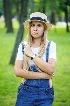 Młoda piękna dziewczyna w dżinsowych kombinezonach i lekkim kapeluszu spacerująca po parku