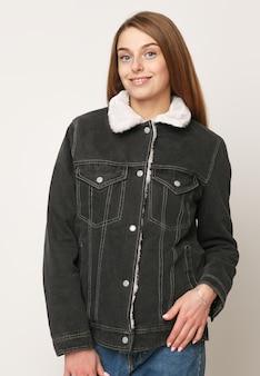 Młoda piękna dziewczyna w dżinsowym szarym swetrze na białym tle .. pojęcie piękna i mody, pojęcie dżinsy.
