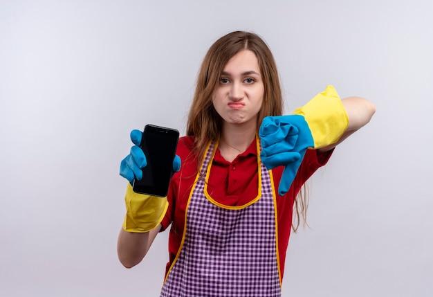 Młoda piękna dziewczyna w fartuch i gumowe rękawiczki pokazuje smartfon niezadowolony pokazując kciuki w dół