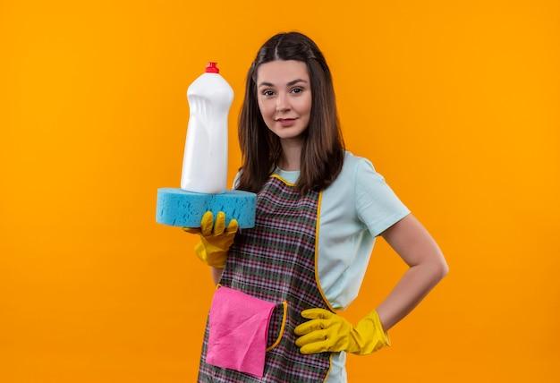 Młoda piękna dziewczyna w fartuch i gumowe rękawiczki, trzymając środki czystości i gąbkę, patrząc na kamery, uśmiechając się pewnie
