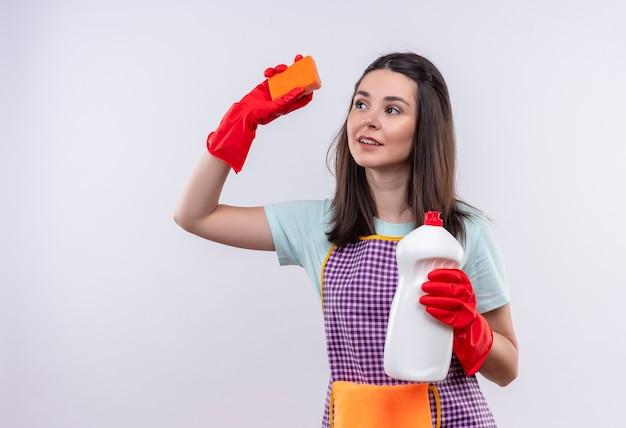 Młoda piękna dziewczyna w fartuch i gumowe rękawiczki, trzymając środki czystości i gąbkę, uśmiechając się pewnie, idzie do czyszczenia