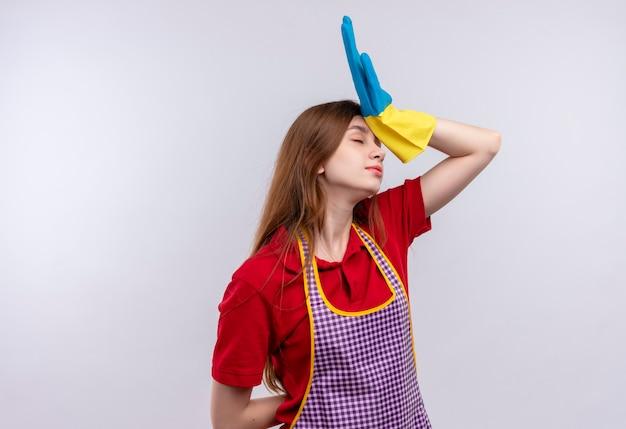 Młoda piękna dziewczyna w fartuch i gumowe rękawiczki wyglądająca na zmęczoną i przepracowaną ręką na głowie