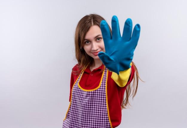 Młoda piękna dziewczyna w fartuch i gumowe rękawiczki z otwartą ręką co znak stopu