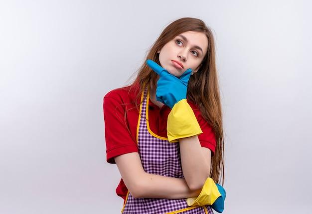 Młoda piękna dziewczyna w fartuch i rękawice gumowe patrząc ręką na brodzie z zamyślonym wyrazem