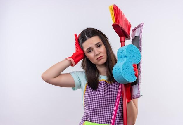 Młoda piękna dziewczyna w fartuch i rękawice gumowe, trzymając narzędzia do czyszczenia, wyglądająca na zmęczoną i przepracowaną, mając ból głowy