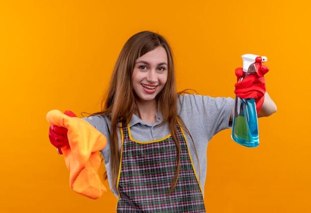 Młoda piękna dziewczyna w fartuch i rękawice gumowe, trzymając spray do czyszczenia i dywan patrząc na aparat uśmiechnięty, gotowy do czyszczenia