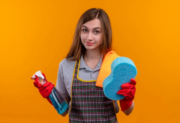 Młoda piękna dziewczyna w fartuch i rękawice gumowe, trzymając spray do czyszczenia i gąbkę, patrząc na aparat uśmiechnięty, gotowy do czyszczenia
