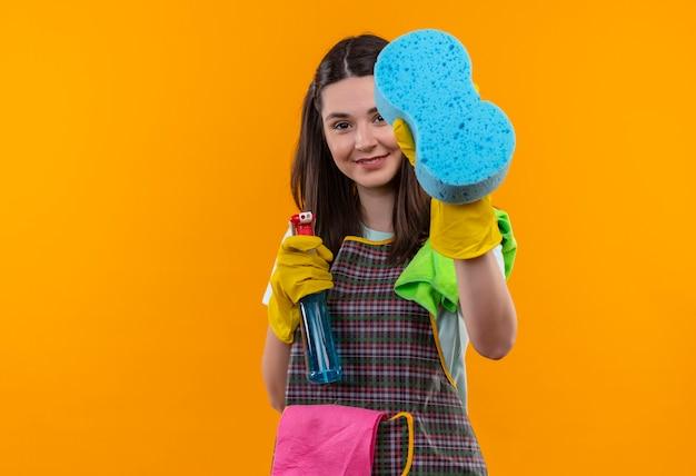 Młoda piękna dziewczyna w fartuch i rękawice gumowe, trzymając spray do czyszczenia i gąbkę, patrząc na aparat uśmiechnięty z radosną buźką, gotowy do czyszczenia