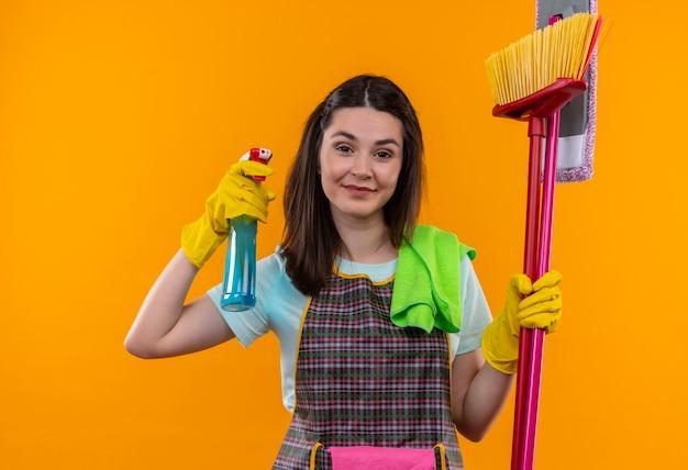 Młoda piękna dziewczyna w fartuch i rękawice gumowe, trzymając spray do czyszczenia i mopy, uśmiechając się pewnie, idzie do czyszczenia