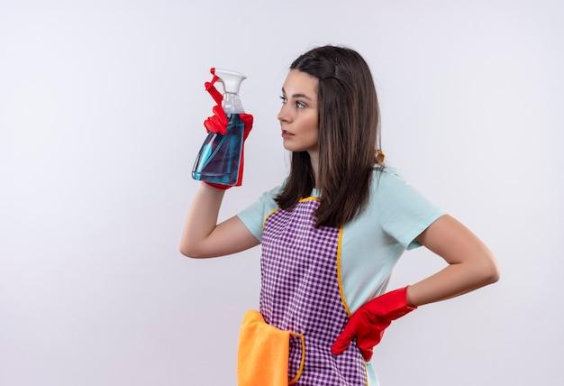 Młoda piękna dziewczyna w fartuch i rękawice gumowe trzymając spray do czyszczenia, patrząc na bok z poważną miną