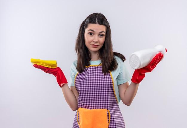 Młoda piękna dziewczyna w fartuch i rękawice gumowe, trzymając środki czystości i gąbkę, patrząc zdezorientowany wzruszając ramionami