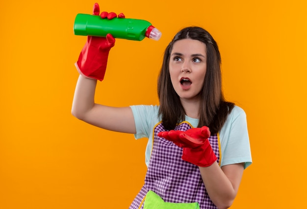 Młoda piękna dziewczyna w fartuch i rękawice gumowe, trzymając środki czyszczące wlewając się do ramienia, patrząc zaskoczony