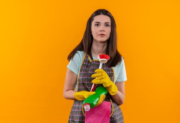 Młoda piękna dziewczyna w fartuch i rękawice gumowe, trzymając szczotkę do szorowania i supermocarstwo patrząc na bok z poważnymi facelies