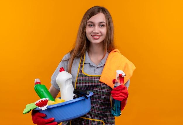 Młoda piękna dziewczyna w fartuch i rękawice gumowe, trzymając umywalkę z narzędziami do czyszczenia i spray z dywanikiem uśmiechnięty szczęśliwy i pozytywny