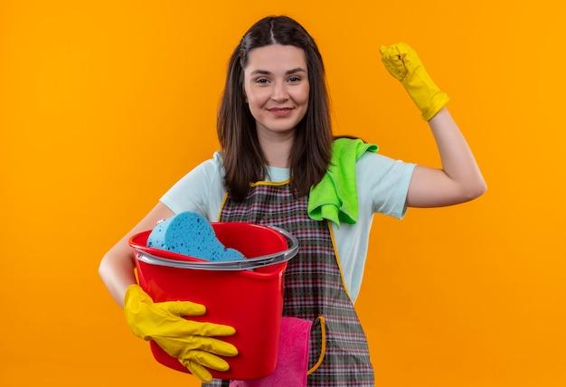 Młoda piękna dziewczyna w fartuch i rękawice gumowe, trzymając wiadro z narzędziami do czyszczenia, podnosząc pięść jak uśmiechnięty zwycięzca