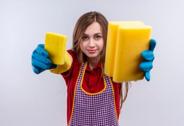 Młoda piękna dziewczyna w fartuch i rękawiczki gumowe pokazując gąbki do aparatu uśmiechnięty
