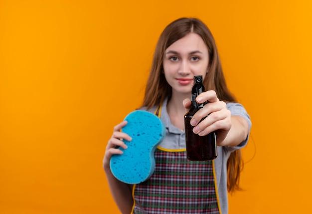 Młoda piękna dziewczyna w fartuch trzymając spray do czyszczenia i gąbkę patrząc na aparat uśmiechnięty przyjazny, gotowy do czyszczenia