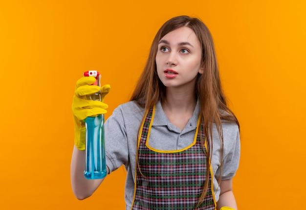 Młoda piękna dziewczyna w fartuch trzymając spray do czyszczenia patrząc na bok, idzie do czyszczenia