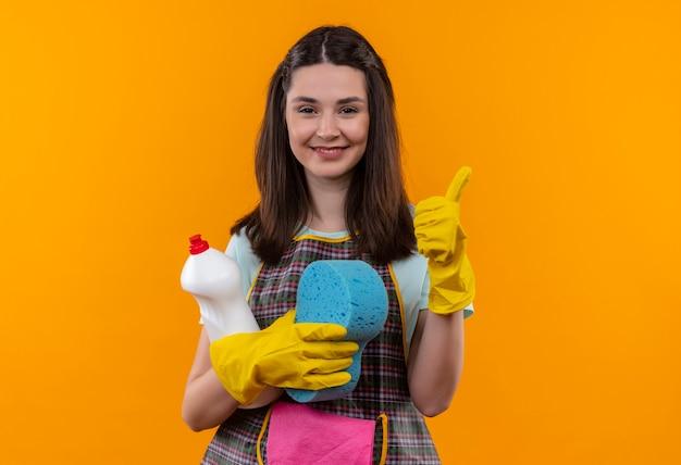Młoda piękna dziewczyna w fartuchu i gumowych rękawiczkach trzyma przybory do czyszczenia i gąbkę patrząc na kamerę, uśmiechając się wesoło, pokazując kciuki do góry