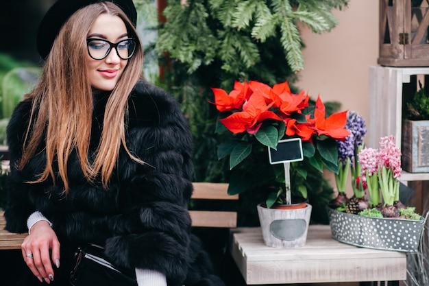 Młoda piękna dziewczyna w futerkowym żakiecie pozuje siedzieć przy sklepem z kwiatami na ulicie w zima czasie
