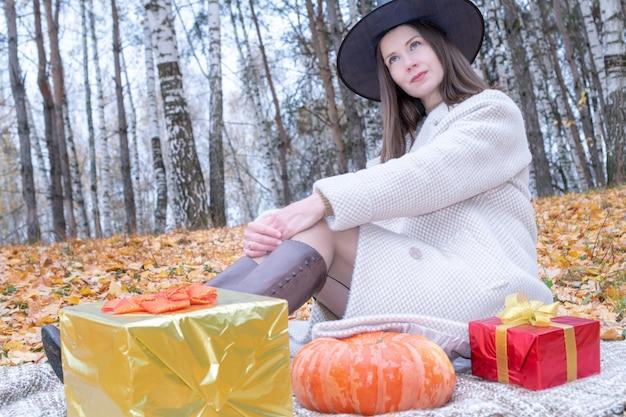 Młoda piękna dziewczyna w kapelusz czarownicy i stylowy płaszcz