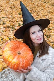 Młoda piękna dziewczyna w kapeluszu czarownicy i stylowym płaszczu trzyma w rękach dużą dynię
