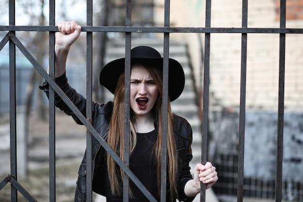Młoda piękna dziewczyna w kapeluszu iz ciemnym makijażem na zewnątrz. dziewczyna w stylu gotyckim na ulicy. dziewczyna idzie ulicą miasta w skórzanej kamizelce z telefonem.