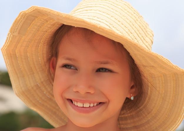 Młoda piękna dziewczyna w kapeluszu mrużąc oczy przed słońcem.