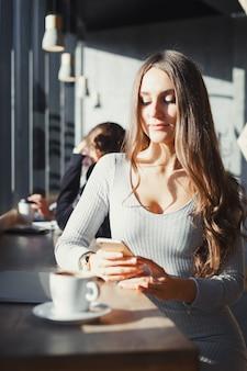 Młoda piękna dziewczyna w kawiarni używa smartfona