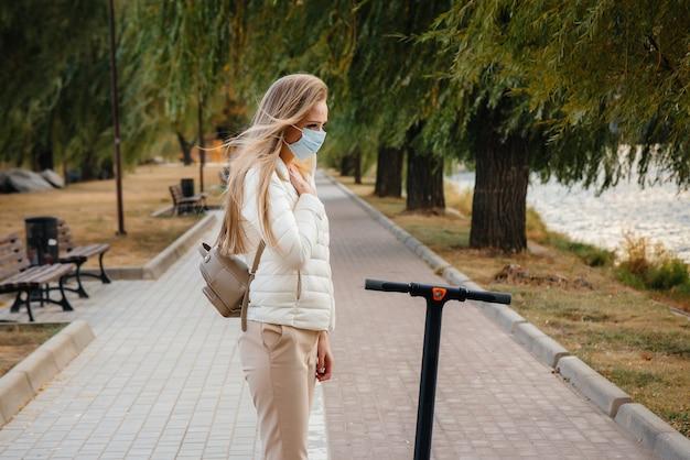 Młoda piękna dziewczyna w masce jedzie po parku na skuterze elektrycznym w ciepły jesienny dzień. spacerować w parku.
