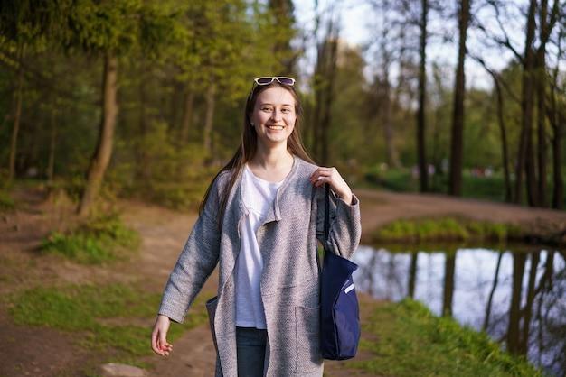 Młoda piękna dziewczyna w okularach przeciwsłonecznych i niosąca torbę spaceruje po leśnym parku nad jeziorem w słoneczny dzień