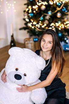 Młoda piękna dziewczyna w pobliżu choinki z wielkim białym misiem uśmiecha się radośnie