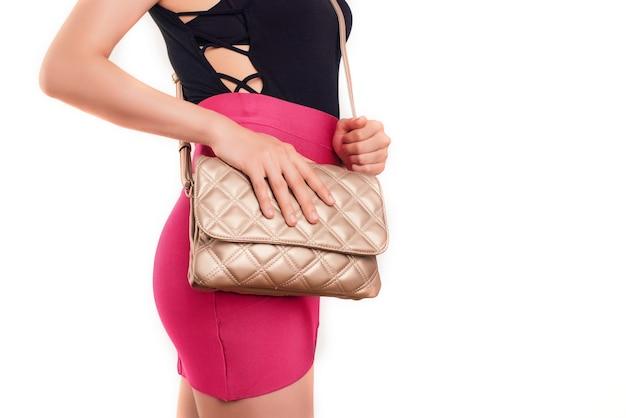 Młoda piękna dziewczyna w różowej spódnicy z brązową torebką. stylowa torebka w rękach kobiety.