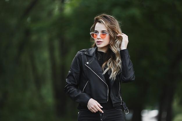 Młoda piękna dziewczyna w skórzanej kurtce i modnych okularach przeciwsłonecznych chodzi samotnie na zewnątrz w letni dzień