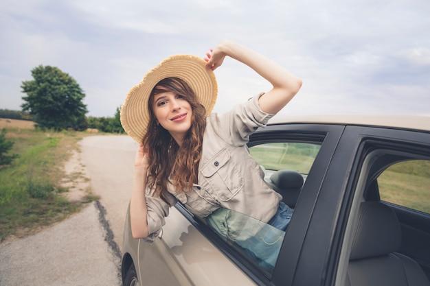 Młoda piękna dziewczyna w słomkowym kapeluszu na okno samochodzie