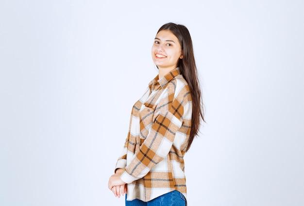 Młoda piękna dziewczyna w stroju casual pozowanie na białej ścianie.